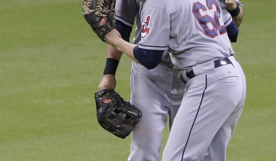 Cleveland Indians' Tyler Holt (62) hugs Michael Brantley after the Indians beat the Houston Astros 2-1 in 13 innings of baseball, Thursday, Sept. 18, 2014, in Houston. (AP Photo/Pat Sullivan)