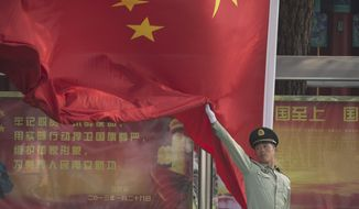 A Chinese paramilitary policeman practices for a flag raising ceremony at a barrack near Tiananmen Gate in Beijing, China, Friday, Sept. 19, 2014. Hundreds of thousands foreign and domestic tourists are expected to flock to the square to celebrate National Day, the 65th anniversary of the founding of People's Republic of China, on Oct. 1. (AP Photo/Vincent Thian)