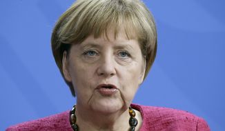 German Chancellor Angela Merkel addresses the media during a joint press conference with the President of the Philippines, Benigno S. Aquino III., as part of a meeting at the chancellery in Berlin, Germany, Friday, Sept. 19, 2014. (AP Photo/Michael Sohn)