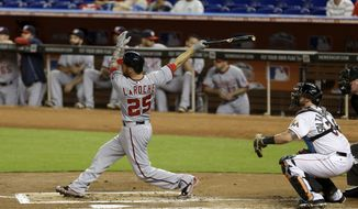 Washington Nationals' Adam LaRoche (25) follows through on a two-run home run against the Miami Marlins in the first inning of a baseball game in Miami, Friday, Sept. 19, 2014. Nationals' Jayson Werth also scored on the home run. (AP Photo/Alan Diaz