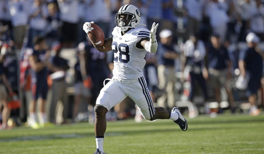 Brigham Young's Adam Hine (28) celebrates after scoring on a 100-yard kickoff return against Virginia in the fourth quarter during an NCAA college football game Saturday, Sept. 20, 2014, in Provo, Utah. BYU won 41-33. (AP Photo/Rick Bowmer)