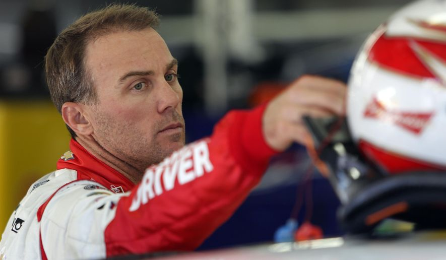 Driver Kevin Harvick reaches for his helmet as he gets ready for practice for Sunday's NASCAR Sprint Cup Series auto race at New Hampshire Motor Speedway, Friday, Sept. 19, 2014, in Loudon, N.H. (AP Photo/Jim Cole)