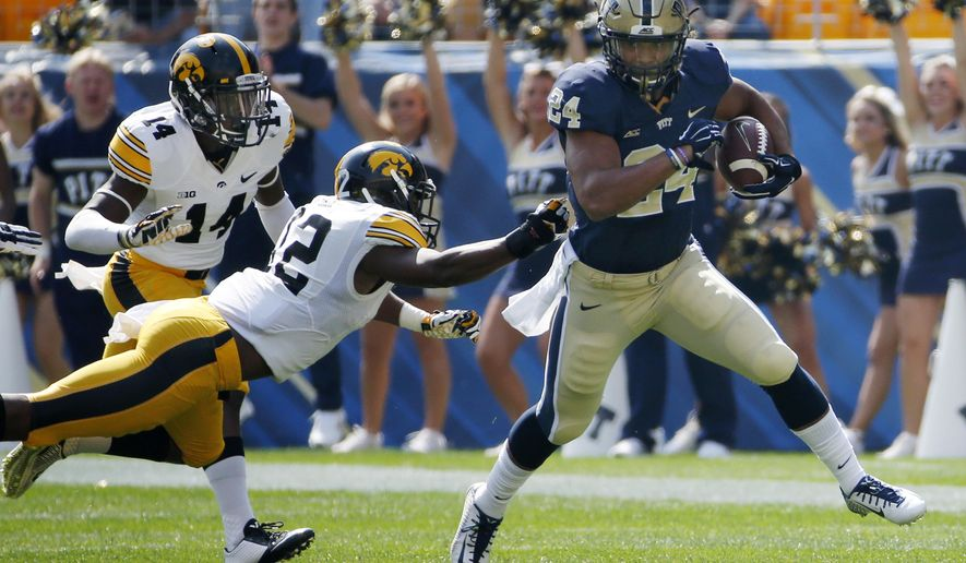 Pitt running back James Conner (24) eludes the tackle of Iowa defensive back Anthony Gair (12) during a first-quarter run in an NCAA college football game in Pittsburgh, Saturday, Sept. 20, 2014. (AP Photo/Gene Puskar)
