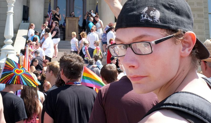 In a photo from Aug. 23, 2014, people rally at the State House in Lansing, Mich., as part of the Michigan Pride Parade and Rally. A push to update Michigan's anti-discrimination law to include protections for gay, lesbian, bisexual and transgender residents is stalled, as Republicans insist it would have to include religious liberty exemptions and Democrats say it is not negotiable. (AP Photo/Lansing State Journal, Robert Killips)