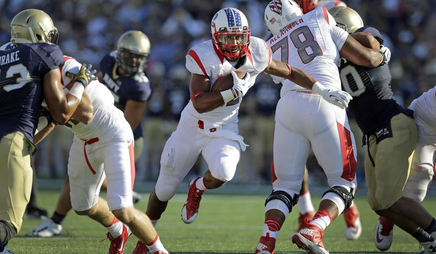 Rutgers running back Justin Goodwin, center, rushes through a hole in the first half of an NCAA college football game against Navy in Annapolis, Md., Saturday, Sept. 20, 2014. (AP Photo/Patrick Semansky)