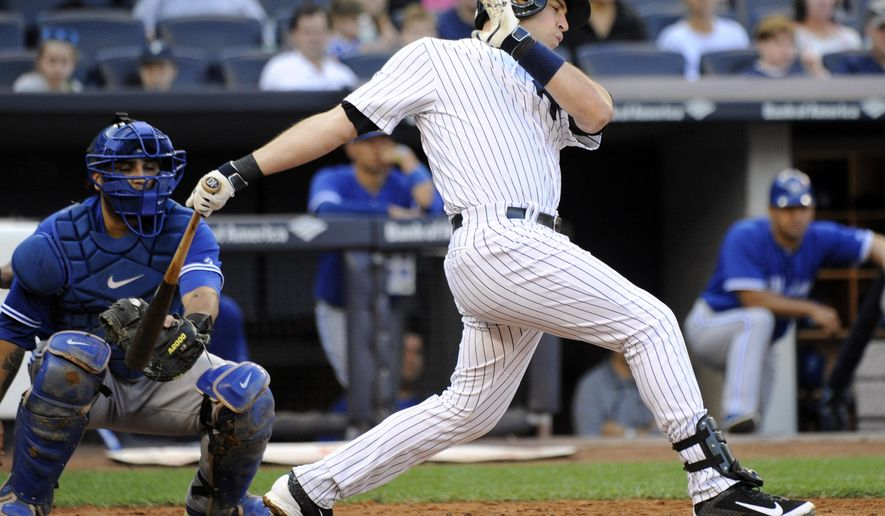 New York Yankees' Mark Teixeira strikes out as Toronto Blue Jays catcher Dioner Navarro, left, looks on during the third inning of a baseball game Saturday, Sept. 20, 2014, at Yankee Stadium in New York. Teixeira left the game with a wrist injury. (AP Photo/Bill Kostroun)