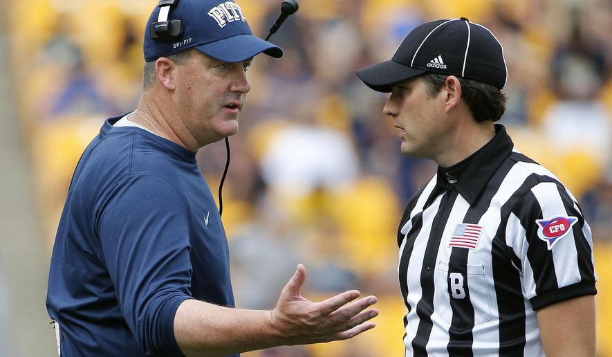 Pitt head coach Paul Chryst, left, talks with an official late in the fourth quarter of an NCAA college football game against Iowa in Pittsburgh, Saturday, Sept. 20, 2014. Iowa won 24-20. (AP Photo/Gene Puskar)