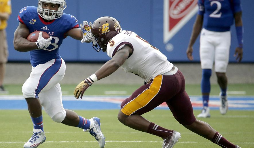Kansas running back De'Andre Mann (23) tries to get past Central Michigan defensive back Kavon Frazier (5) during the first half of an NCAA college football game Saturday, Sept. 20, 2014, in Lawrence, Kan. (AP Photo/Charlie Riedel)