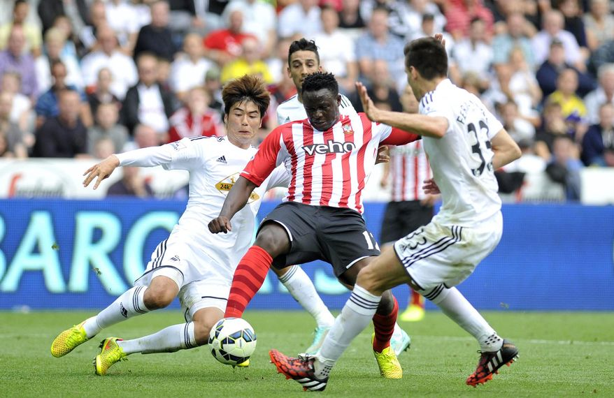 Southampton's Victor Wanyama, center, scores as Swansea City's Ki Sung-Yueng tries to challenge during the English Premier League soccer match at the Liberty Stadium, Swansea, Wales, Saturday Sept. 20, 2014. (AP Photo/PA) UNITED KINGDOM OUT  NO SALES  NO ARCHIVE
