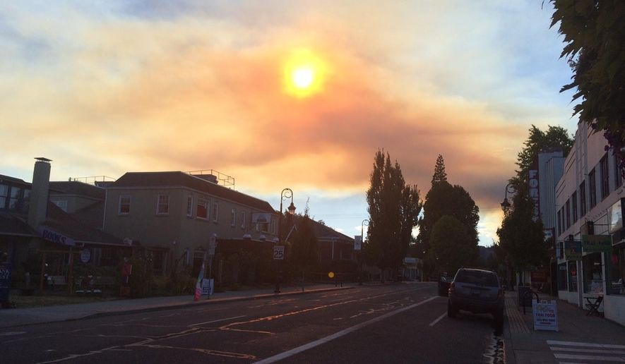 Smoke from a fire north of Hagg Lake can be seen in downtown Forest Grove, Ore., on Friday, Sept. 19, 2014. (AP Photo/The Oregonian, Samantha Swindler)