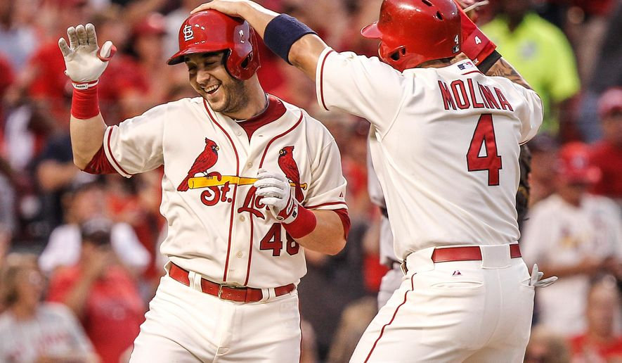 St. Louis Cardinals' Yadier Molina, right, congratulates teammate Tony Cruz, left, on his three-run home run during the second inning of a baseball game against the Cincinnati Reds, Saturday, Sept. 20, 2014, in St. Louis. (AP Photo/Sarah Conard)