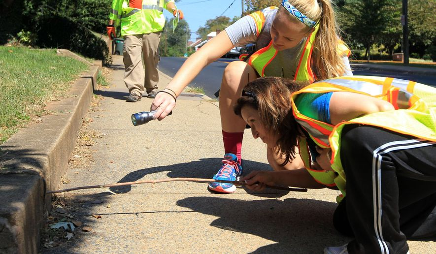 Volunteers Caroline Robinson, left, and Callie Robinson, right, use a stick and a flashlight to probe inside a drainage pipe on 14th Street during a massive search effort by the community for missing University of Virginia student Hannah Graham, Saturday, Sept. 20, 2014, in Charlottesville, Va. (AP Photo/The Daily Progress, Andrew Shurtleff)