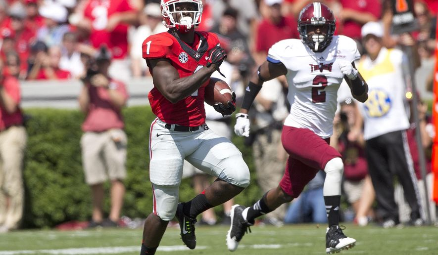 Georgia running back Sony Michel (1) breaks free for a gain as Troy cornerback Keion Payne (2) gives chase in the first half of an NCAA college football game Saturday, Sept. 20, 2014, in Athens, Ga. (AP Photo/John Bazemore)