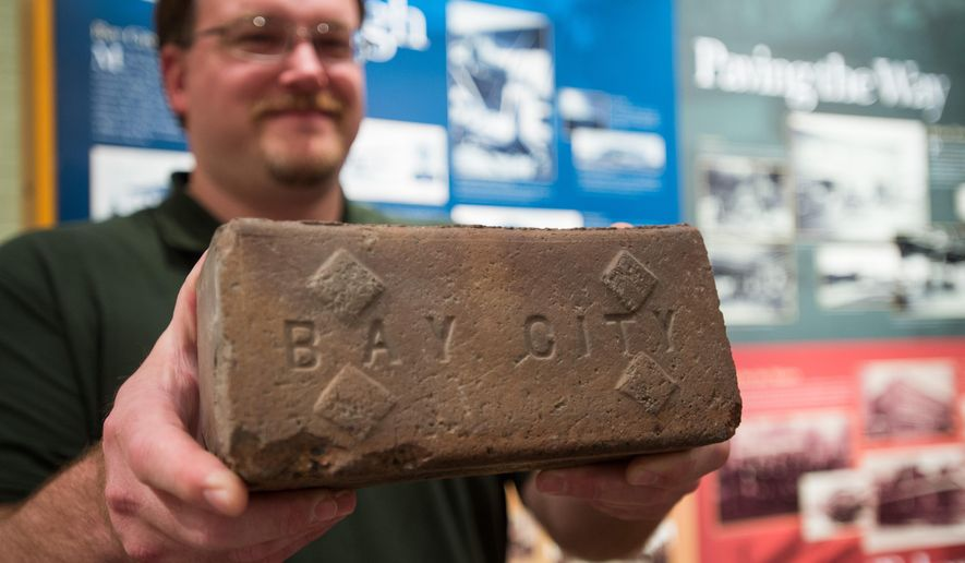 In this photo taken on Thursday, Sept. 18, 2014, Bay County Historical Museum director Ron Bloomfield holds up a 100-year-old brick that was dug up by Consumers Energy subcontractor on Ninth Street between Washington and Saginaw avenues in Bay City, Mich. (AP Photo/The Bay City Times, Yfat Yossifor) LOCAL TELEVISION OUT; LOCAL INTERNET OUT