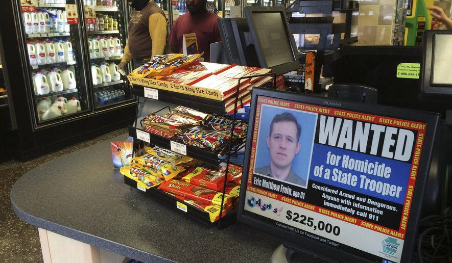 A video display at a convenience store shows a wanted poster of Eric Frein, a 31-year-old from Canadensis, Pa., Friday, Sept. 19, 2014, in Philadelphia. Frein is charged with killing Pennsylvania State Trooper Cpl. Bryon Dickson and wounding Trooper Alex Douglass in a late-night ambush Sept. 12 outside the Blooming Grove state police barracks. (AP Photo/Matt Slocum)