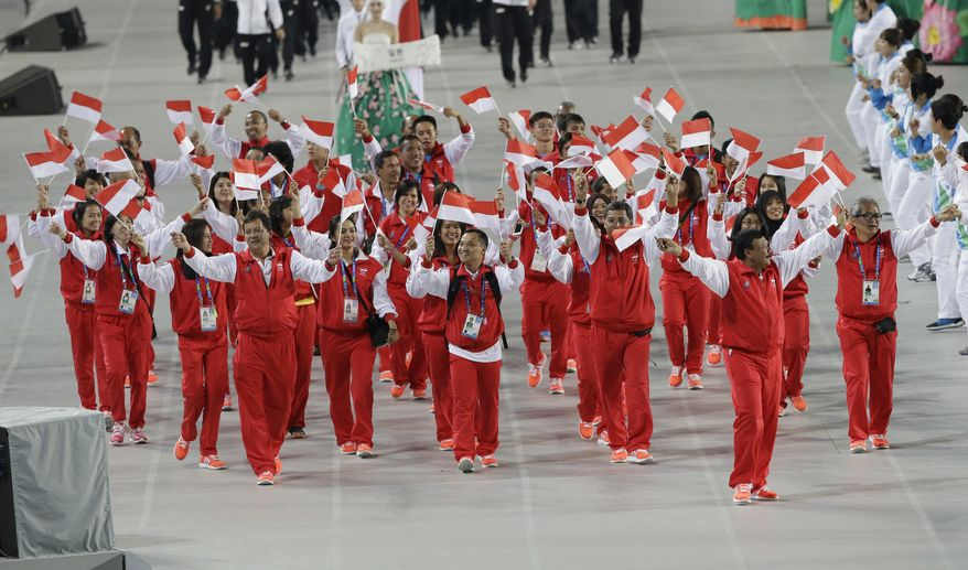 Athletes from Indonesia march into the stadium during the opening ceremony for the 17th Asian Games in Incheon, South Korea,Friday, Sept. 19, 2014. (AP Photo/Dita Alangkara)