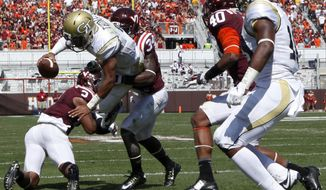 Georgia Tech quarterback Justin Thomas (5) scores a first half touchdown past Virginia Tech's Donovan Riley (2) and Kyshoen Jarrett (34) an NCAA college football game in Blacksburg, Va., Saturday, Sept. 20, 2014. (AP Photo/The Roanoke Times, Matt Gentry)  LOCAL TV OUT; SALEM TIMES REGISTER OUT; FINCASTLE HERALD OUT;  CHRISTIANBURG NEWS MESSENGER OUT; RADFORD NEWS JOURNAL OUT; ROANOKE STAR SENTINEL OUT