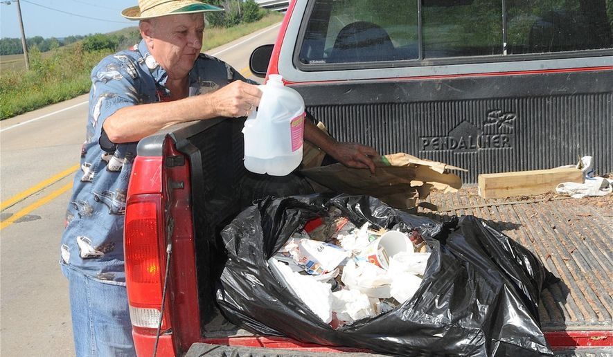 In this Sept. 8, 2014, photo, Bill McGregor, of Fort Madison, Iowa, puts trash he's picked up from the side of the road into the back of his truck in Fort Madison, Iowa. McGregor and two friends, spend several hours a week patrolling areas of the city, trash bags in tow, collecting garbage that has been tossed from moving vehicles. (AP Photo/Fort Madison Daily Democrat, Jeff Hunt)