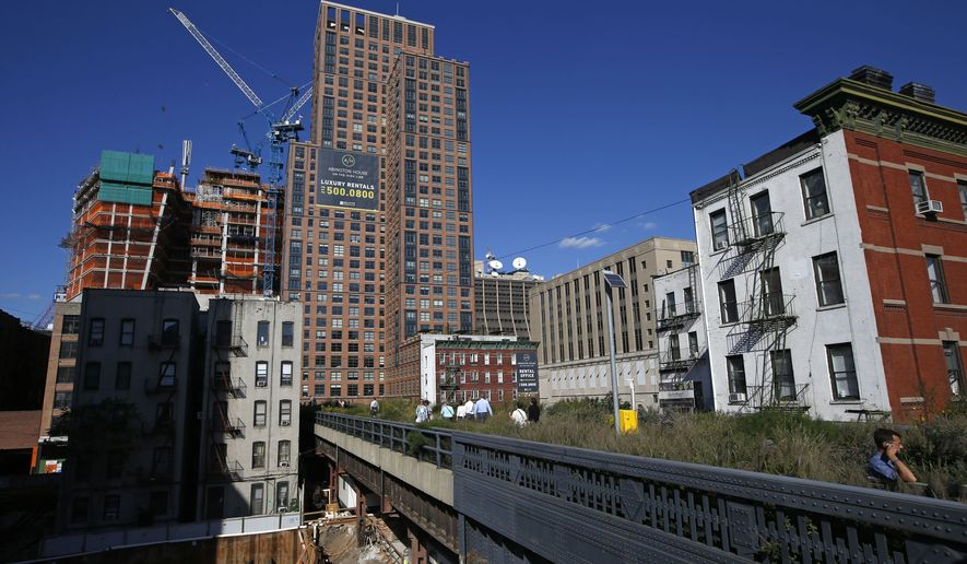 The High Line disappears into luxury high-rise apartment buildings in New York, Wednesday, Sept. 17, 2014. The last stretch of the elevated walkway opens to the public Sunday, Sept. 21. (AP Photo/Kathy Willens)