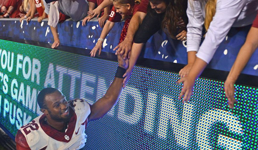 Oklahoma's Samaje Perine slaps hands with fans after an NCAA college football game against West Virginia in Morgantown, W.Va., on Saturday, Sept. 20, 2014. Oklahoma won 45-33. (AP Photo/Tyler Evert)