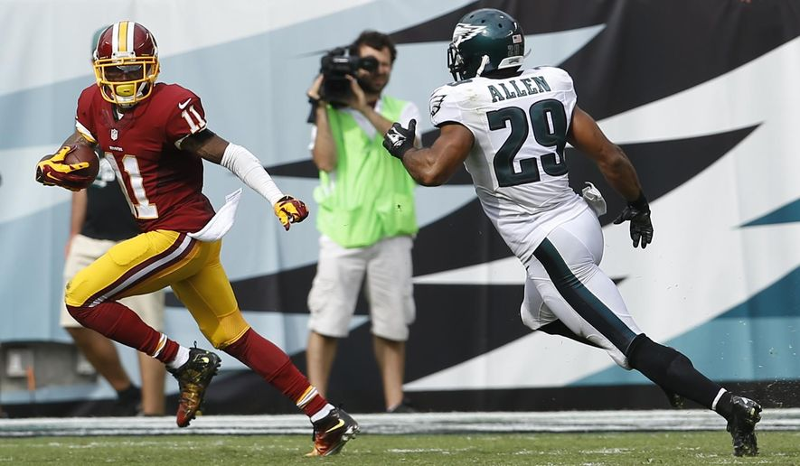 Washington Redskins wide receiver DeSean Jackson (11) looks back as Philadelphia Eagles strong safety Nate Allen (29) chases after him on a scoring reception during the second half of an NFL football game, Sunday, Sept. 21, 2014, in Philadelphia. (AP Photo/Michael Perez)