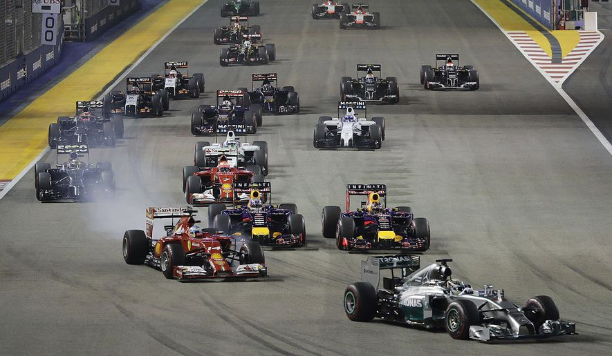 Mercedes driver Lewis Hamilton of Britain, front, leads the field with Ferrari driver Fernando Alonso of Spain, front left, following close into turn one at the start of the Singapore Formula One Grand Prix on the Marina Bay City Circuit in Singapore, Sunday, Sept. 21, 2014. (AP Photo/Wong Maye-E)
