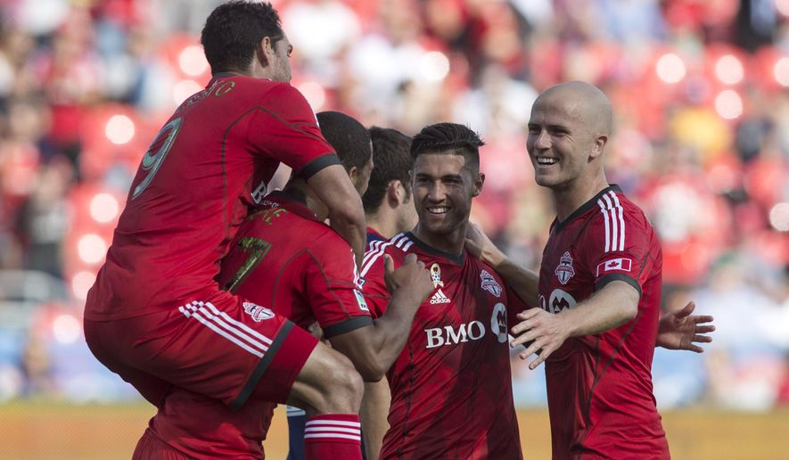 Toronto FC 's Gilberto, left, climbs onto Luke Moore's back as Moore celebrates with Jonathan Osorio, second from right. and Michael Bradley, right, after scoring his team's second goal against Chivas USA during the first half of an MLS soccer game in Toronto on Sunday, Sept. 21, 2014. (AP Photo/The Canadian Press, Chris Young)