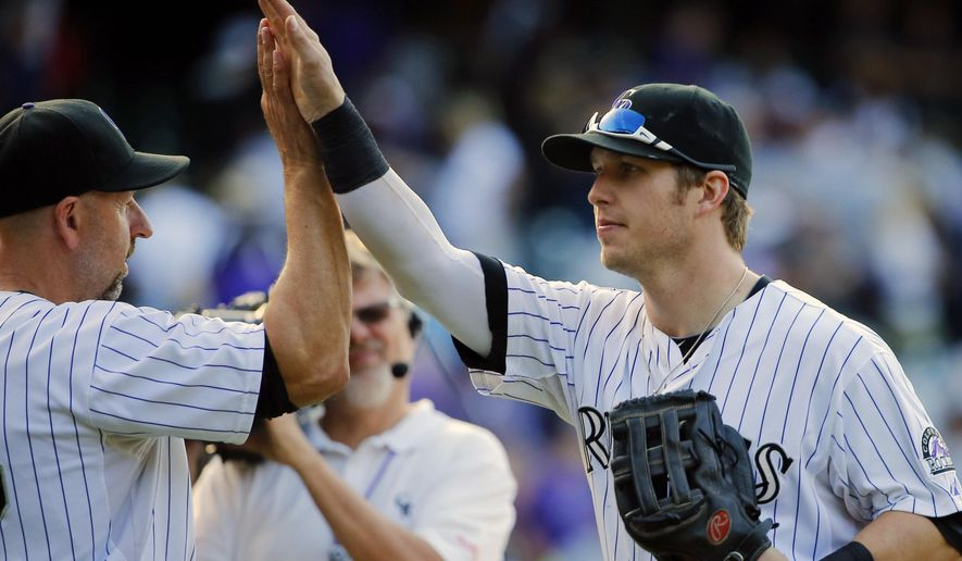Colorado Rockies' Corey Dickerson, right, high-fives manager Walt Weiss following a baseball game against the Arizona Diamondbacks, Saturday, Sept. 20, 2014, in Denver. The Rockies won 5-1.  (AP Photo/Jack Dempsey)