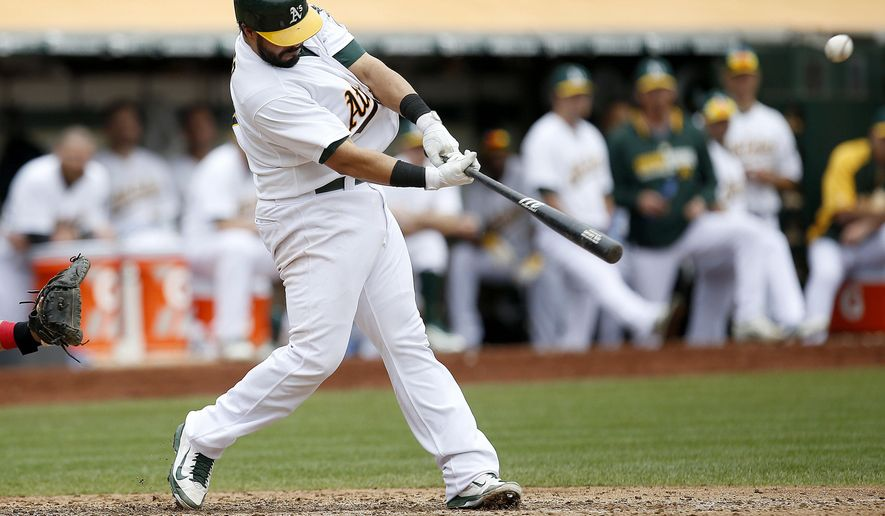 Oakland Athletics' Geovany Soto hits a double to drive in two runs against the Philadelphia Phillies in the fifth inning of a baseball game Sunday, Sept. 21, 2014, in Oakland, Calif. (AP Photo/Tony Avelar)
