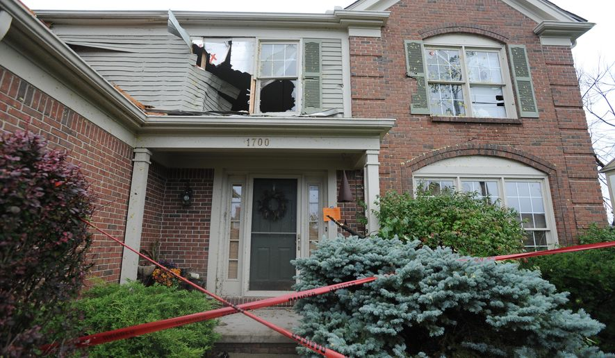 A damaged home on Grandview Drive. Residents, emergency workers and the curious check out the damage from a tornado that struck Grandview Drive in Rochester Hills, Mich., Sunday, Sept. 21, 2014. (AP Photo/Detroit News, Brandy Baker)