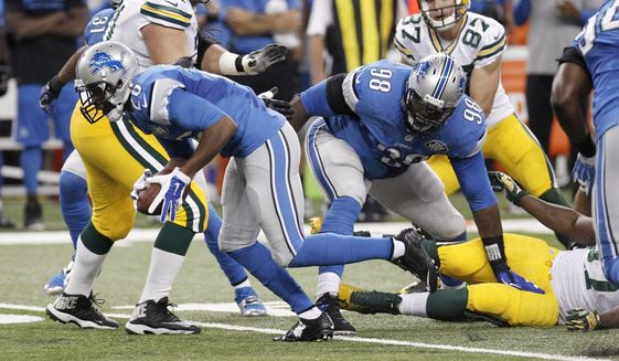 Detroit Lions strong safety Don Carey, front left, picks up a fumble by Green Bay Packers running back Eddie Lacy and runs it back for a 40-yard touchdown during the first half of an NFL football game in Detroit, Sunday, Sept. 21, 2014. (AP Photo/Duane Burleson)
