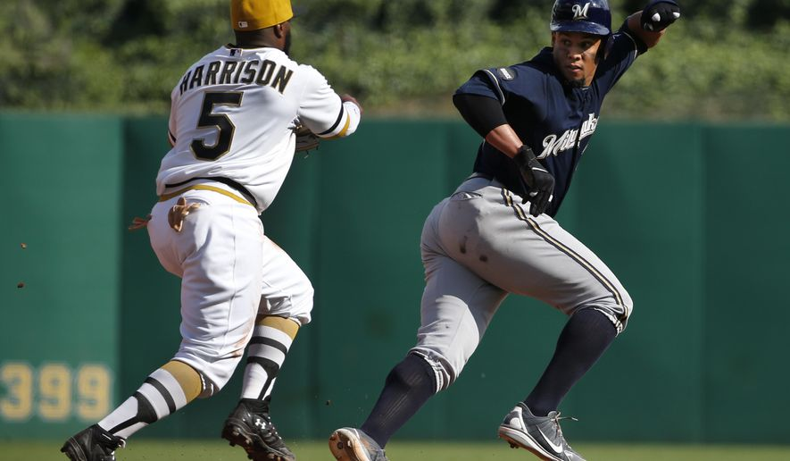 Pittsburgh Pirates third baseman Josh Harrison (5) runs down Milwaukee Brewers' Carlos Gomez between second and third during the ninth inning of a baseball game in Pittsburgh, Sunday, Sept. 21, 2014. Harrison tagged Gomez out to end the rundown and the Pirates won 1-0. (AP Photo/Gene J. Puskar)