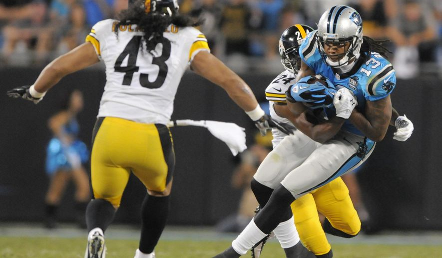 Carolina Panthers' Kelvin Benjamin (13) runs as Pittsburgh Steelers' Ike Taylor (24) wraps him up and Troy Polamalu (43) closes in during the first half of an NFL football game in Charlotte, N.C., Sunday, Sept. 21, 2014. (AP Photo/Mike McCarn)