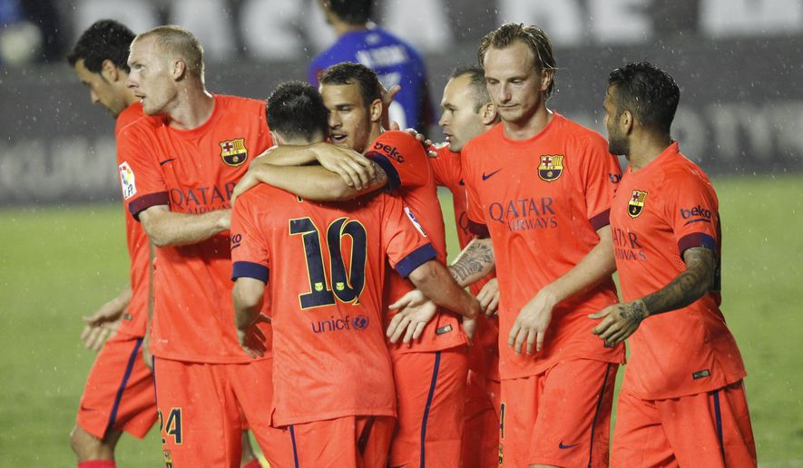 Barcelona's Sandro, center celebrates a with teammates after scoring against Levante during a Spanish La Liga soccer match at the Ciutat de Valencia stadium in Valencia, Spain, on Sunday, Sept. 21, 2014. (AP Photo/Alberto Saiz)