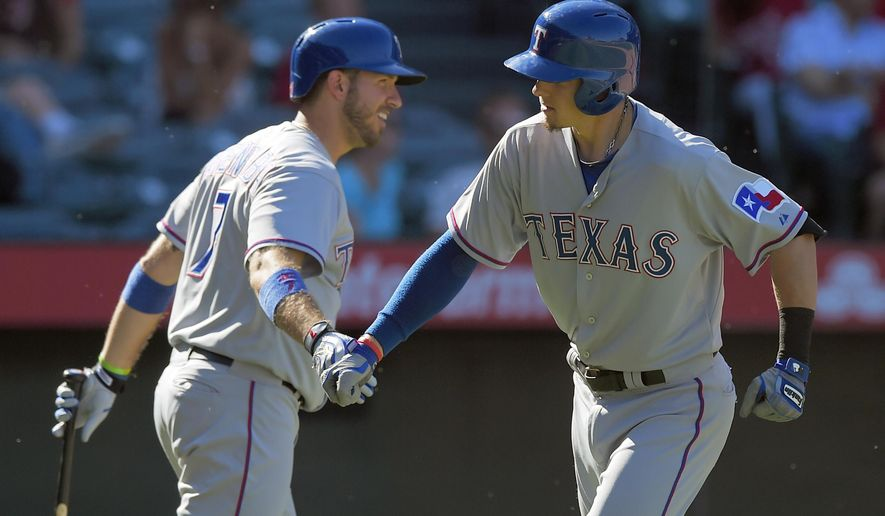 Texas Rangers' Ryan Rua, right, is congratulated by teammate J.P. Arencibia on his solo home run against the Los Angeles Angels in the ninth inning of a baseball game in Anaheim, Calif., Sunday, Sept. 21, 2014. The Rangers won 2-1. (AP Photo/Mark J. Terrill)