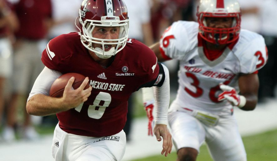 New Mexico State quarterback Tyler Rogers outruns New Mexico defender Brandon Branch to the end zone for a touchdown during the second quarter of an NCAA college football game Saturday Sept. 20, 2014 in Las Cruces, N.M. (AP Photo/Victor Calzada)