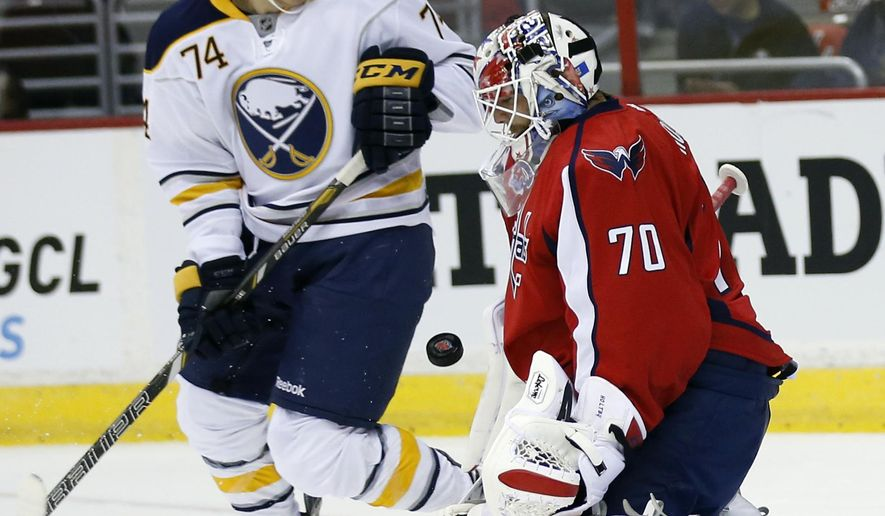Washington Capitals goalie Braden Holtby (70) deflects a shot with Buffalo Sabres left wing Vaclav Karabacek (74) nearby, in the second period of a preseason NHL hockey game, Sunday, Sept. 21, 2014, in Washington. (AP Photo/Alex Brandon)