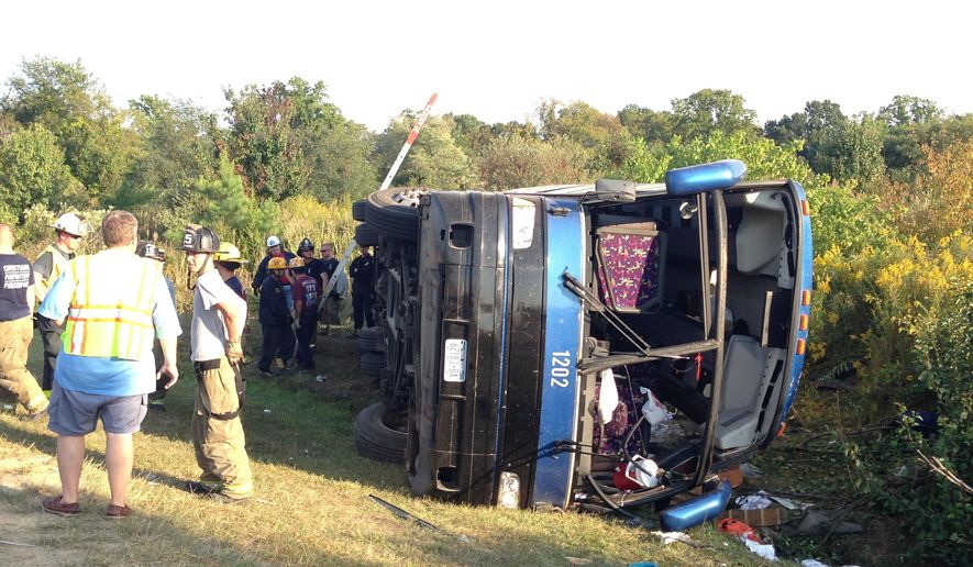 Passengers from a tour bus are treated for injuries near the overturned bus at the Tybouts Corner on ramp from southbound Del. 1 to Red Lion Road. Officials at the scene reported one fatality and several injuries from the crash the 4:20 p.m. crash on Sunday, Sept. 21, 2014, in Bear, Del. (AP Photo/The Wilmington News-Journal, John J. Jankowski)