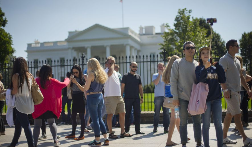 Tourist stop to take their photograph in front of the White House in Washington, Saturday, Sept. 20, 2014.  The Secret Service is coming under renewed scrutiny after a man scaled the White House fence and made it all the way through the front door before he was apprehended. (AP Photo/Pablo Martinez Monsivais)