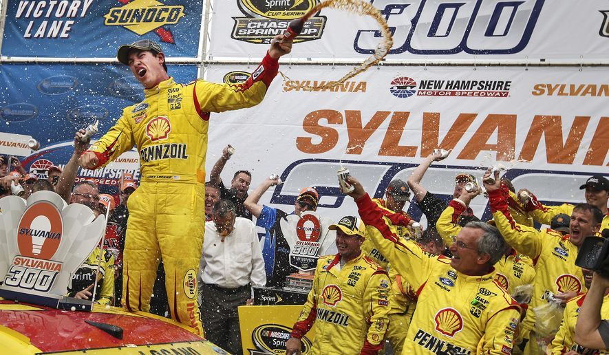 Joey Logano celebrates in Victory Lane after winning the NASCAR Sprint Cup series auto race at New Hampshire Motor Speedway, in Loudon, N.H., Sunday, Sept. 21, 2014. (AP Photo/Cheryl Senter)