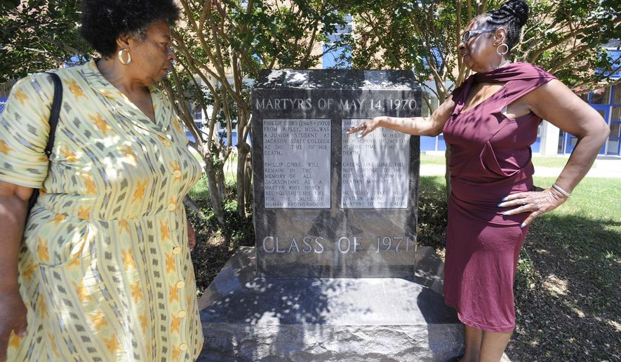 ADVANCE FOR SUNDAY SEPT. 21   This photo taken July 30, 2014, shows sisters Mattie Hull, left, and Gloria Green-McCray looking at a memorial to their late brother, James Earl Green, at Jackson State University in Jackson, Miss. The teenager was fatally shot by law enforcement during a campus protest in 1970, and they would like his death to being investigated under the Emmett Till Act if the law is expanded someday to allow reviews of deaths that happened after 1969. (AP Photo/Jay Reeves)