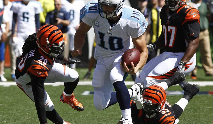 Tennessee Titans quarterback Jake Locker (10) runs for a first down past Cincinnati Bengals free safety Reggie Nelson (20) and defensive end Wallace Gilberry (95) in the first half of an NFL football game, Sunday, Sept. 21, 2014, in Cincinnati. (AP Photo/David Kohl)