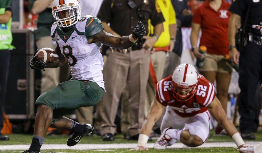 Miami running back Duke Johnson (8) runs past Nebraska linebacker Josh Banderas (52) in the first half of an NCAA college football game in Lincoln, Neb., Saturday, Sept. 20, 2014. (AP Photo/Nati Harnik)