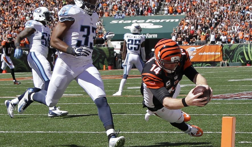 Cincinnati Bengals quarterback Andy Dalton (14) dives into the end zone for a touchdown past Tennessee Titans free safety Michael Griffin (33) in the first half of an NFL football game, Sunday, Sept. 21, 2014, in Cincinnati. (AP Photo/Darron Cummings)