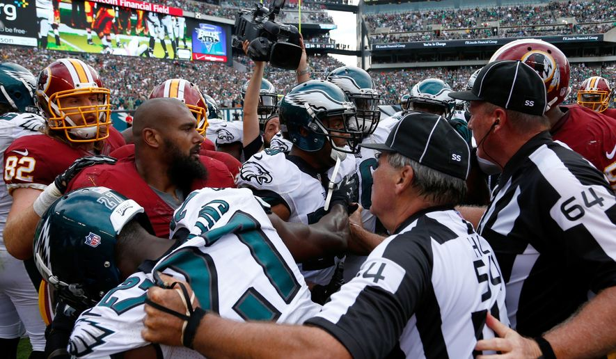 Officials try to break up a scuffle between the Washington Redskins and Philadelphia Eagles during the second half of an NFL football game, Sunday, Sept. 21, 2014, in Philadelphia. (AP Photo/Matt Rourke)