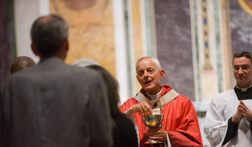 Cardinal Donald W. Wuerl, Archbishop of Washington, offers Communion during a Mass commemorating the 75th anniversary of the Archdiocese of Washington. (khalid naji-allah/special to the washington times)
