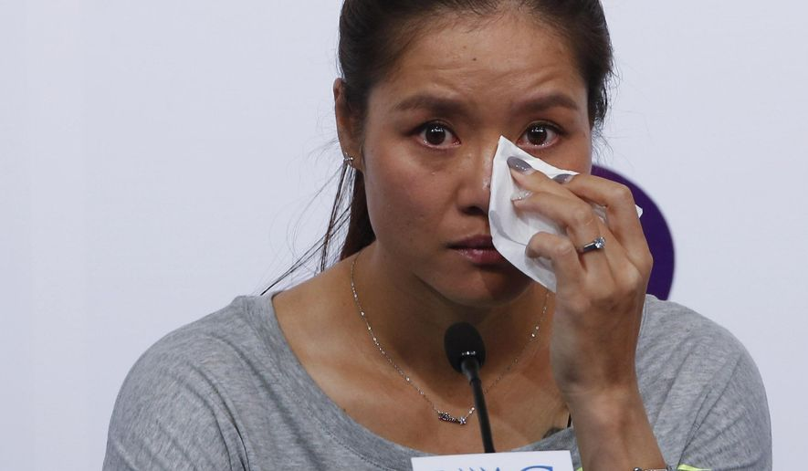 Chinese tennis player Li Na wipes her tears during a press conference to announce  her retirement in Beijing, China, Sunday, Sept. 21, 2014. The two-time Grand Slam champion from China who took tennis in Asia to a new level, has retired due to recurring knee injuries.  (AP Photo/Vincent Thian)