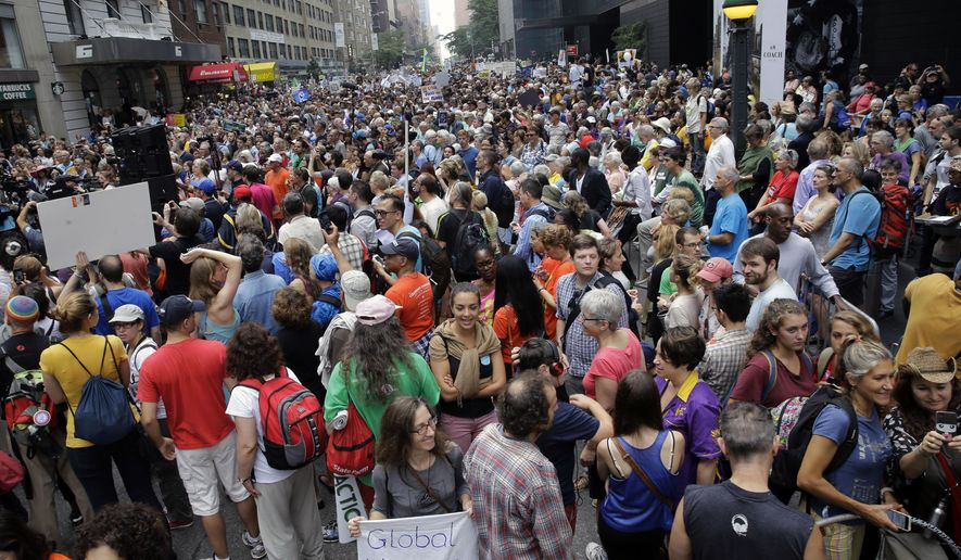 People fill 58th Street between 8th and 9th Avenue  in New York before a climate change protest march Sunday, Sept. 21, 2014. Thousands of people from across the nation are expected in New York City to participate in what's billed as the largest march ever on global warming. (AP Photo/Mel Evans)