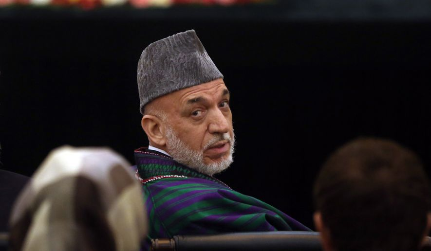 Afghanistan's President Hamid Karzai looks back during a ceremony for signing a power-sharing deal between two presidential candidates, at the presidential palace in Kabul, Afghanistan, Sunday, Sept. 21, 2014. Afghanistan's two presidential candidates signed a power-sharing deal Sunday, capped with a hug and a handshake, three months after a disputed runoff that threatened to plunge the country into turmoil and complicate the withdrawal of U.S. and foreign troops. (AP Photo/Massoud Hossaini)