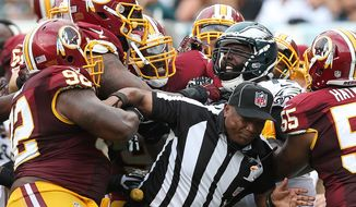 Philadelphia Eagles' Jason Peters, right, and Washington Redskins' Chris Baker, left, tussle after a fourth-quarter play as line judge Darryll Lewis tries to break it up during an NFL football game Sunday, Sept. 21, 2014, in Philadelphia. Both players were ejected. Philadelphia won 37-34. (AP Photo/Philadelphia Daily News, David Maialetti)